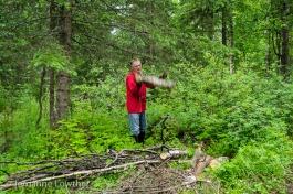 Dean Kalbfleisch tosses log on firewood pile.