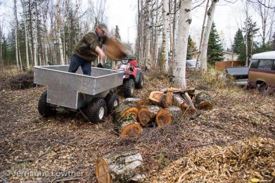 Elliott Marlow unloads firewood from ATV trailer at Creekside trailhead.