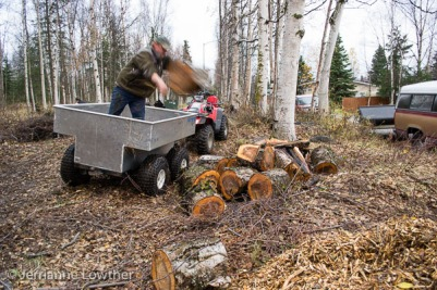 Elliott Marlow unloads firewood from ATV trailer at Creekside trailhead.
