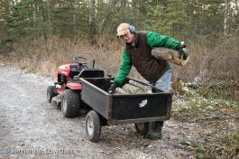 Dean Kalbfleisch unloads firewood logs at Creekside trailhead.